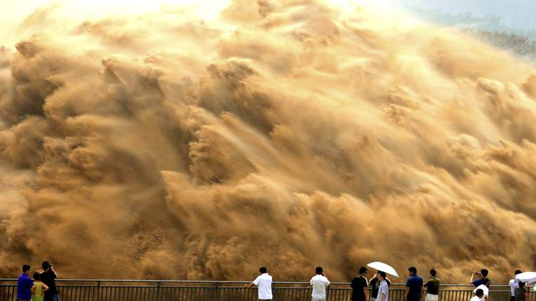Visitors watch water gushing from the section of the Xiaolangdi Reservoir on the Yellow River, during a sand-washing operation in Jiyuan